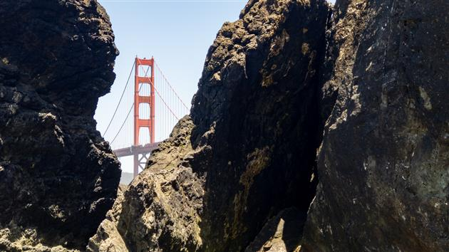 Golden Gate Bridge framed by rocks on Marshall's Beach